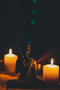 Buddha by the candles symbolising peace and healing