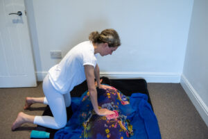 Tatiana Aitken giving tantric massage to client who has come in for yoni massage therapy